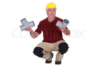 Plumber holding two pipes