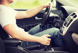 man shifting the gear on car manual gearbox