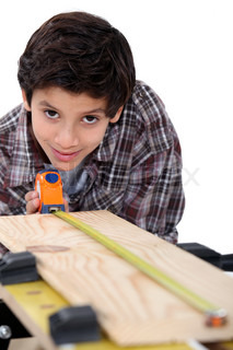 Boy carpenter measuring wood