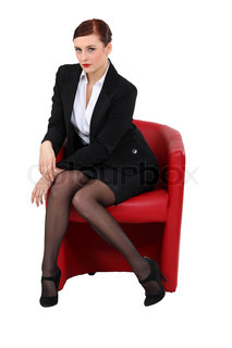 classy brunette with mysterious gaze sitting on red armchair