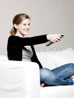 A smiling teenage girl surfing the TV with a remote control