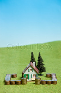 Miniature house surrounded by coins