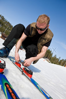 A man fixing his pair of ski