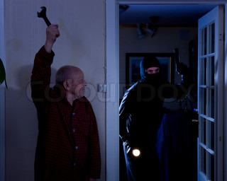 An elderly man ready to attack a burglar