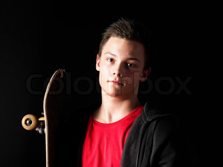 Portrait of a young man holding a skate