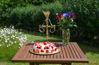 Homemade strawberry cake at a summer decorated table in a garden with daisies