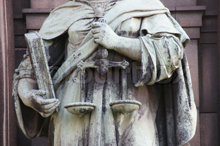 Statue to justice and learning showing a book and sales of justice