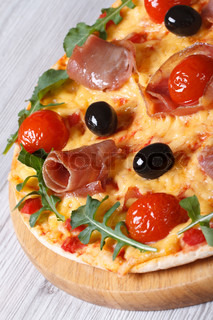 Pizza with ham, tomatoes, cheese, olives and arugula