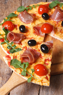 Sliced pizza with ham, tomatoes,  olives and arugula vertical