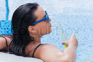 Young woman portrait relaxing and having a drink in a swimming pool