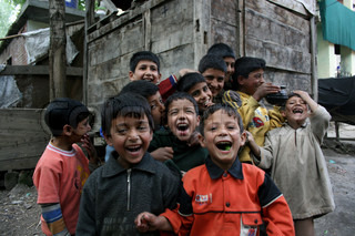 Kashmiri Muslim childrens smile as they look at camera  in the outskirts of Srinagar, India Kashmir. The 20-year old turmoil in Indian Kashmir badly h