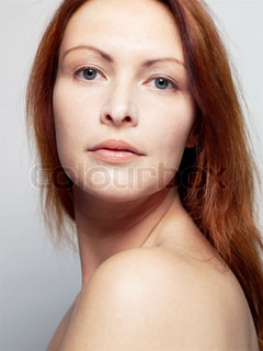 Portrait of a red-haired woman with bare shoulders
