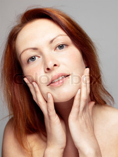 Portrait of a red-haired woman touching her face