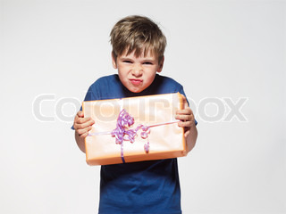 A disappointed-looking boy holding a birthday present