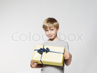 A young blond boy holding a birthday present