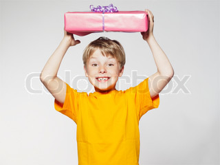 A smiling young boy holding a birthday present on top of his head