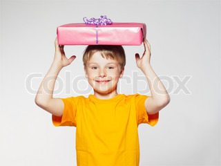 A smiling young boy holding a birthday gift on top of his head