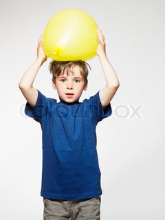 A young boy holding a yellow balloon
