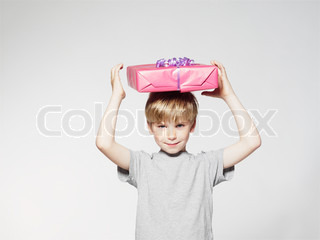 A young boy holding a birthday present on top of his head