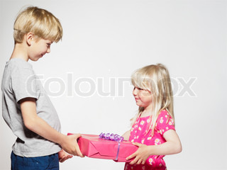 A young girl receives a birthday present from her brother