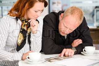 A caucasian couple looking at brochure of houses for sale