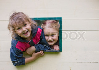Happy faces of girls on a window