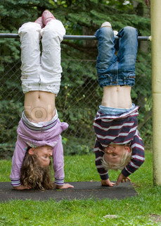 Children hanging upside down in a playground pole