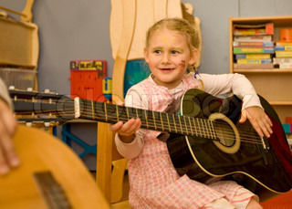 A young girl learns to play the guitar