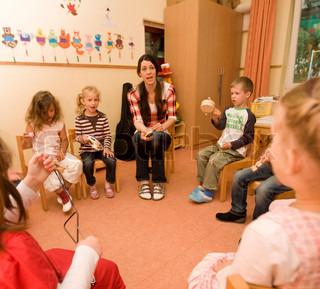A teacher teaching kindergarten students to play music