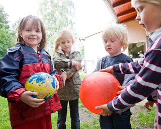 A group of children playing with  balloons