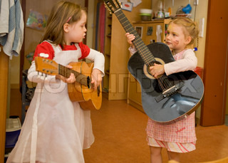 Two young girls in kindergarten playing guitar