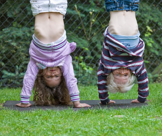 Children in upside down position while playing on a pole