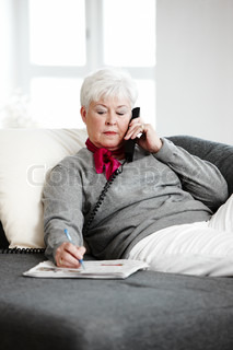 An elderly caucasian woman sitting on the sofa and talking on the phone