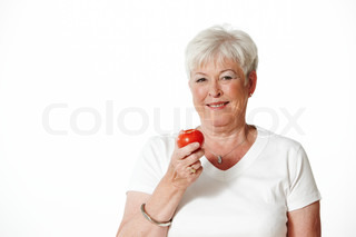 Elderly smiling woman holding tomato