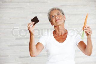 An elderly woman holding a chocolate bar and a carrot