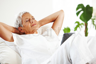 An elderly caucasian woman relaxing on a sofa