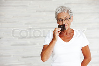 An elderly woman smelling a bar of chocolate