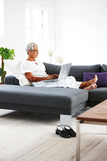 An elderly caucasian woman sitting on a sofa with a laptop