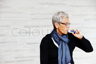 An elderly caucasian woman who is taking her temperature