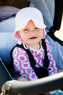 A baby girl with summer hat sitting on a pram