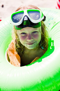 A caucasian girl with green goggles and floater