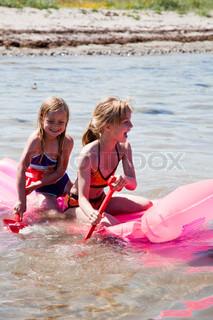 Two girls rowing aboard a plastic  boat