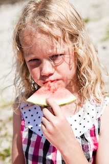Caucasian girl eating watermelon during a summer picnic