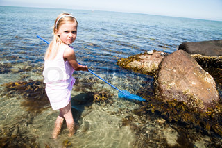 A girl in the beach with a net for catching fish