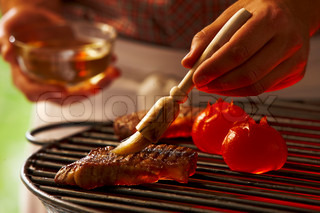 A man applying marinade on meat  on the grill