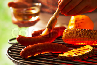 Barbecuing sausages, corn and mixed vegetables