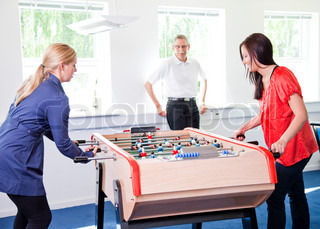 Business people having fun i the break/ recreation room.  Colleagues playing tabletop football in the break room of their office. Business people havi