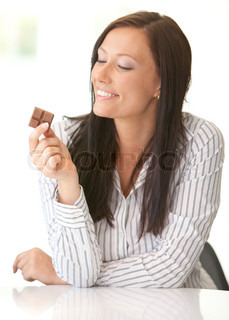 Woman eating a piece of chocolate.