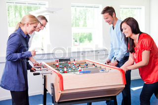 4 colleagues playing tabletop football in the break room of their office. Business people having fun i the break/ recreation room.