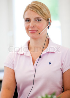 Businesswoman in the customer care or sales departement talking to customers/ clients.